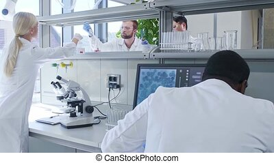 Scientist and students working in lab. Doctor teaching interns to make analyzing research. Laboratory tools: microscope, test tubes, equipment. Biotechnology, chemistry, bacteriology, virology.