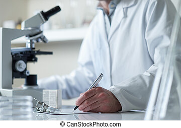 scientist conducting research with microscope selective...