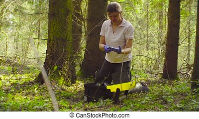 Scientist ecologist in the forest taking samples of moss