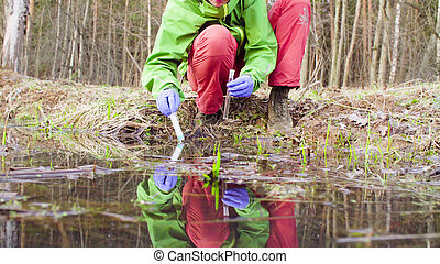 Scientist ecologist in the forest taking samples of water