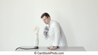Scientist engineer is testing robotic prosthesis hand which...