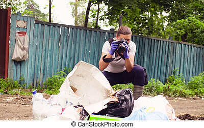 Scientist environmentalist making photos of garbage dump.