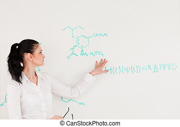 Scientist explaining a formula written on a white board to...