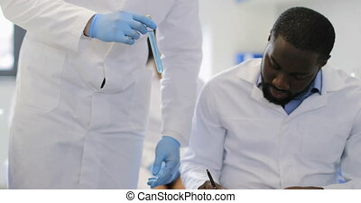 Scientist Hold Test Tube While Group Of Researchers Making Notes Of Experiment In Modern Laboratory