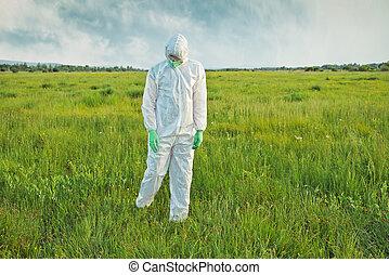 Scientist in biohazard uniform on summer field