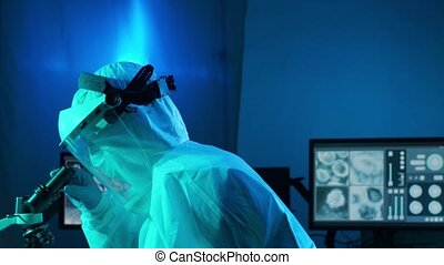 Scientist in protection suit and masks working in research lab using laboratory equipment: microscopes, test tubes. Coronavirus 2019-ncov hazard, pharmaceutical discovery, bacteriology and virology concept.