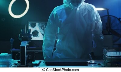Scientist in protection suit and masks working in research lab using laboratory equipment: microscopes, test tubes. Coronavirus SARS-CoV-2 hazard, pharmaceutical discovery, bacteriology and virology.