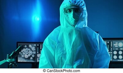Scientist in protection suits and masks working in research lab using laboratory equipment: microscopes, test tubes. Coronavirus covid-19 hazard, pharmaceutical discovery, bacteriology and virology concept.