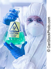 Scientist in protective suit with hazardous chemical in...