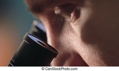 Scientist looking through a microscope in a laboratory. Young doctror diagnostic close up shot