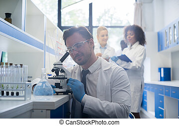 Scientist Looking Through Microscope In Laboratory, Male Researcher Doing Experiments Over Team Of Female Researchers Discussing Research