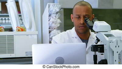 Scientist looking through microscope while using laptop 4k