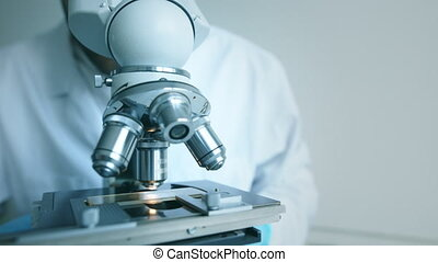 Scientist looks into microscope - Young scientist looks to...