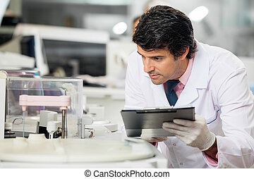 Scientist Observing Experiment - Male scientist observing...