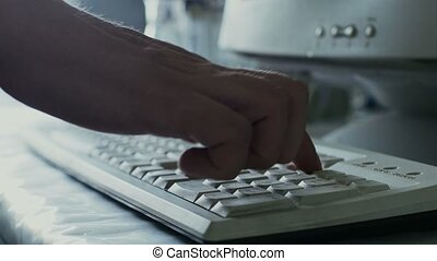 scientist or medical researcher enters data on keyboard into...