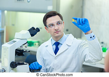 Scientist studies properties and benefits of omega 3 fatty acids using microscope and laboratory equipment in a medical laboratory