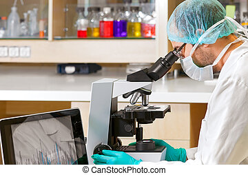 Scientist using a computer and microscope.