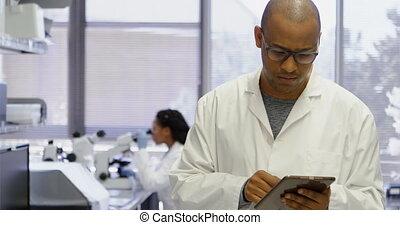 Scientist using digital tablet 4k - Scientist using digital...