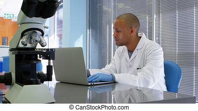 Scientist using laptop 4k - Scientist using laptop in office...