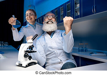 scientist using microscope while colleague holding reagent in tube in lab. scientists working together in laboratory
