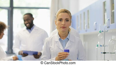 Scientist Woman Hold Bottle With Chemical Liquid Happy Smiling Over Talking Researchers Mix Race Team In Modern Laboratory