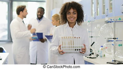 Scientist Woman In Laboratory Portrait Of African American Girl Hold Test Tubes With Chemicals Over Doctors Team Talking Making Notes About Research In Lab