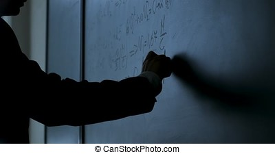 Scientist writing formulas on chalkboard. Hand with chalk...