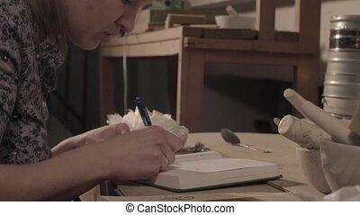 Scientist writing something in notebook.