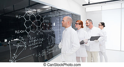 scientists analyzing formulas in lab - side-view of four...
