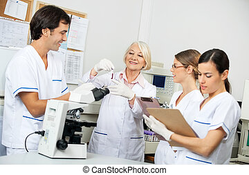 Scientists Discussing Over Blood Sample In Laboratory