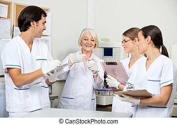 Scientists Discussing Over Sample In Laboratory