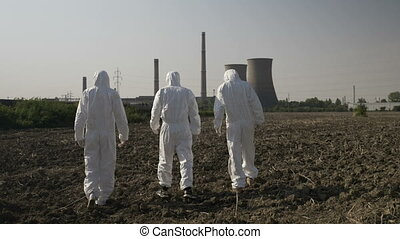 Scientists dressed in hazmat suits carefully walking across a contaminated field near a power plant
