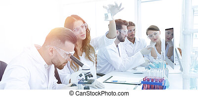 Scientists examining attentively pipette with blue fluid in laboratory..photo with copy space