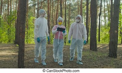Scientists in biohazard suits examining level of radiation...