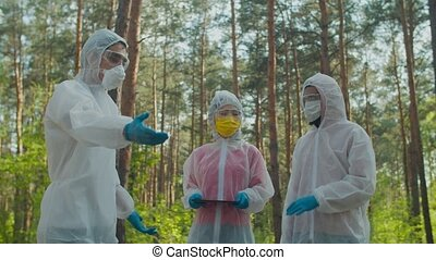 Professional diverse scientists in protective suits and masks with digital tablet exploring biohazard zone, measuring radiation level , discussing data and contamination in danger area.