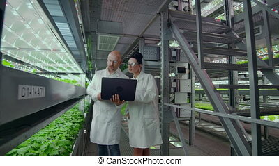 Scientists in white coats with a laptop and a tablet on a...