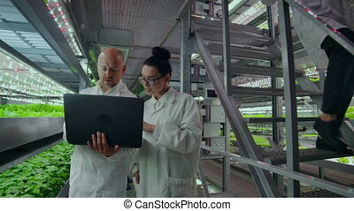 Scientists in white coats with a laptop go along the...