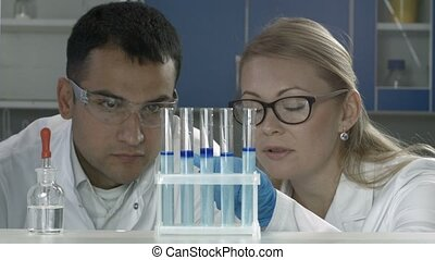 Scientists studying substance in test tubes in lab