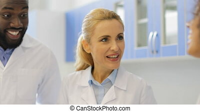 Scientists Team Examine Study Liquid In Test Tube Working On Research At Laboratory, Mix Race Man And Woman Discuss Results Of Experiment In Lab Slow Motion 60