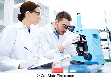 scientists with clipboard and microscope in lab - science,...