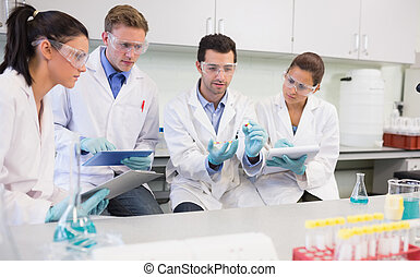 Scientists with tablet PC working on an experiment at lab