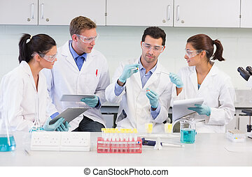 Scientists with tablet PC working on experiment at lab