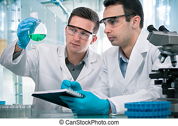 Scientists working in a research laboratory - Two scientists...