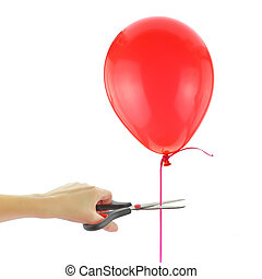 Scissors about to cut loose a balloon isolated on white