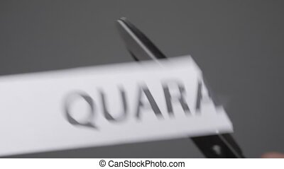 Quarantine is over concept. Scissors cutting a piece of paper with QUARANTINE printed on it. Quarantine is ended. Release from Quarantine. Pandemic of COVID-19 is over. Grey background