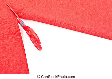 Scissors cutting red paper