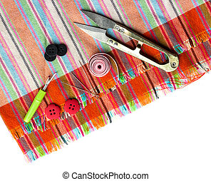 scissors, thread and needle to coarse  canvas of mats on white
