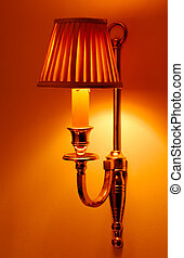 Image shows a lighted sconce delivering warm indoor lighting