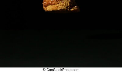 Scone falling on black background in slow motion
