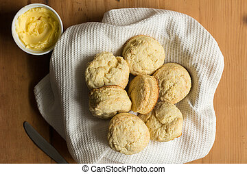 Scones - Biscuits made with buttermilk recipe in bowl with white dish towel, butter and knife on wooden table